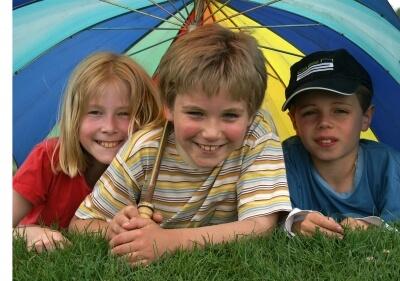 Kinder mit aufgespannten Sonnenschirm (c) S. Hofschlaeger / pixelio.de