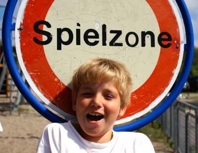 Spiel | Junge vor Schild mit Spielzone (c) S. Hofschlaeger  / pixelio.de