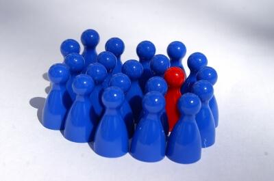 Spielfiguren eine rote und viele blaue (c) Stephanie Hofschlaeger  / pixelio.de
