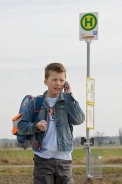 Schule | Junge telefoniert an der Haltestelle (c) eplus.de