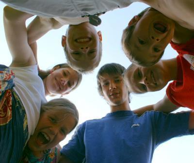 Kinder bilden umarmend einen Kreis (c) S. Hofschlaeger / pixelio.de