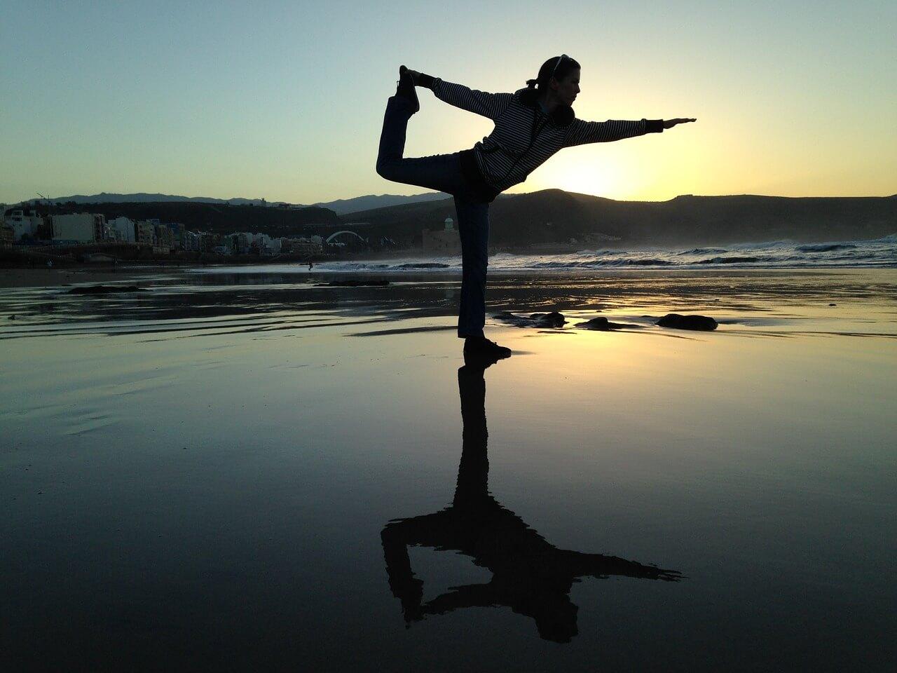 Frau macht am Strand Yoga und findet die richtige Balance